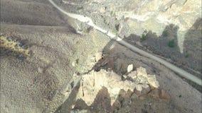 Grusväg med en kurva som videopp passerande över ett av de steniga utlöparna arkivfilmer