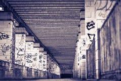 Grusväg med kolonner som målas med grafitti i svartvitt Arkivfoto