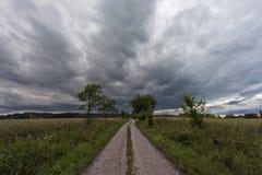 Grusväg och den mörka molniga himlen Fotografering för Bildbyråer
