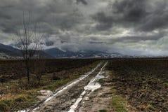Grusväg som leder in i bergen Arkivfoto