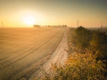 Grusväg som leder in mot soluppgång - åkerbrukt themed Guld- timme för höst arkivbild