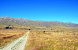 Grusväg som leder till och med jordbruksmark till bergen Royaltyfri Fotografi