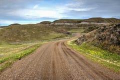 Grusväg som spolar dess väg till och med mycket bergig terräng Fotografering för Bildbyråer