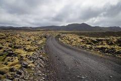 Grusväg till och med vulkaniskt lavafält i Island Arkivfoton