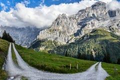 Grusvägvänd i de schweiziska fjällängarna, runt om Grindenwald, med rocen Royaltyfri Bild