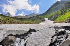 Gruta de la nieve sobre el río de la montaña en el verano Imágenes de archivo libres de regalías