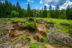 Gruta termal del agua rodeada por la hierba verde Imagen de archivo