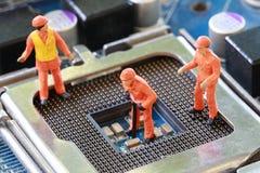 Gruvarbetare arbetar på CPU-håligheten av mainboarden arkivbild
