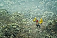 Gruvarbetaren bär korgar med sulphur i dunster av giftlig vulkanisk gas från sulphurminer arkivbilder