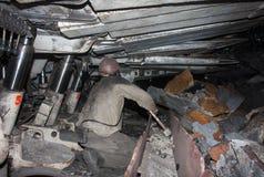 Gruvarbetaren som arbetar i ett begränsat utrymme, gör klar från slaggtransportören Arkivfoton