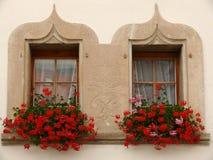 Gruyère, Suíça 07/30/2009 Janelas gêmeas com flores foto de stock royalty free