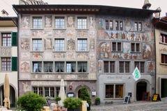 Gruyère, Zwitserland - mag, 2017: De straat van oude stads toeristische plaats, met geschilderd met fresko oude huizen stock afbeeldingen