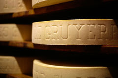Gruyere cheese. Cow milk cheese, stored in a wooden shelves Royalty Free Stock Image