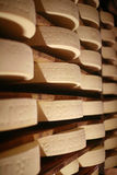 Gruyere cheese. Cow milk cheese, stored in a wooden shelves Stock Photography