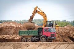 Grävskopan laddar jordningen i lastbilen Arkivfoton