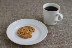 Gryźć ciastko na białym talerzu i kubku kawa Tło Zdjęcia Royalty Free