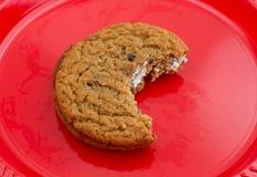 Gryźć oatmeal crème ciastko na czerwonym talerzu Obrazy Royalty Free