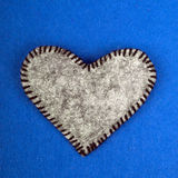 Gry felt heart on a blue background Stock Image