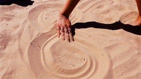 Gry z piaskiem Dziewczyna rysuje na piasku znaka nieskończoność zbiory wideo