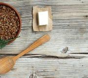 Gryczana owsianka z masłem w glinianym pucharze przeciw drewnianemu tłu Pojęcie: jarski jedzenie, zdrowy kucharstwo Fotografia Royalty Free
