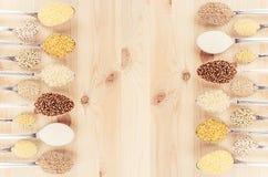 Gryn i skedar på beige wood bräde som dekorativ bakgrund Top beskådar Arkivbild
