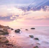 Gryningsoluppgånglandskap över den härliga steniga kustlinjen i havet Royaltyfri Foto