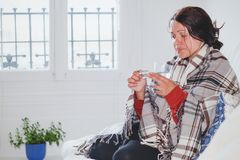 Grypa i febra, chora zimna kobieta bierze medycyn pigułki w domu zdjęcia royalty free