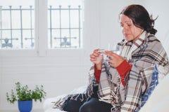 Grypa i febra, chora zimna kobieta bierze medycyn pigułki w domu zdjęcie royalty free