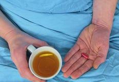 Grypa sezon Ręki mężczyzna mienia pigułka chora filiżanka gorąca herbata w łóżku i Zakończenie chory caucasian mężczyzna przy fotografia royalty free