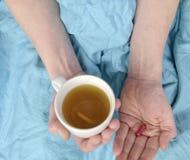 Grypa sezon Ręki mężczyzna mienia pigułka chora filiżanka gorąca herbata w łóżku i Zakończenie chory caucasian mężczyzna przy zdjęcie royalty free