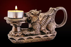 Gryphon candle holder with candle. Gryphon candle holder with lighted candle isolated on dark background Royalty Free Stock Image