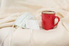 Grypowy sezon domowy karło z szkocką kratą - herbata, medyczna maska, pigułki, tło - fotografia stock