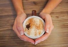 Grzać ręki z Gorącym kubkiem Cappuccino kawa Zdjęcia Stock
