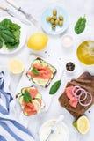 Grzanka ściska z łososiem, kremowym serem, oliwkami i ogórkiem na bielu stole, zdjęcie royalty free