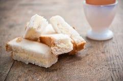 grzanka dotyka z miękka część gotującym się jajkiem w jajecznej filiżance Zdjęcia Royalty Free