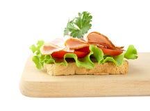 Grzanka, sałata, pomidor, zimni cięcia na tnącej desce na bielu Zdjęcia Stock