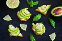 Grzanka z avocado, kremowym serowym curd i wapnem na ciemnym backgro, Fotografia Royalty Free