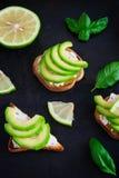 Grzanka z avocado, kremowym serowym curd i wapnem na ciemnym backgro, Zdjęcie Stock