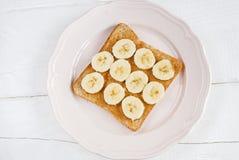Grzanka z domowej roboty masłem orzechowym i bananem na białym stole fotografia stock