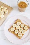 Grzanka z domowej roboty masłem orzechowym i bananem na białym stole zdjęcie stock