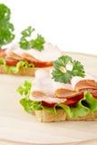 Grzanki, sałata, pomidor, zimni cięcia na tnącej desce na bielu Zdjęcia Stock