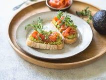 Grzanki z avocado i solonym łososiem z świeżymi groch flancami na talerzu na drewnianej tacy obrazy stock