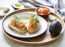 Grzanki z avocado i solonym łososiem z świeżymi groch flancami na talerzu na drewnianej tacy fotografia royalty free