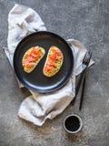 Grzanki z avocado i solonymi sezamowymi ziarnami na czarnym talerzu na szarym tle łososia i czarnych fotografia stock