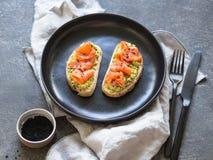 Grzanki z avocado i solonymi sezamowymi ziarnami na czarnym talerzu na szarym tle łososia i czarnych fotografia royalty free
