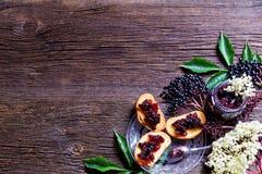 Grzanki z elderberry dżemem i świeżymi jagodowymi owoc na drewnianym stole Uwalnia przestrzeń dla twój teksta Fotografia Royalty Free