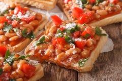Grzanki z fasolami w pomidorowym kumberlandzie, serze i ziele makro-, Hor Zdjęcie Stock