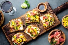 Grzanki z kremowym serem, baleronu jamon serrano i mango, słuzyć na drewnianej desce z czerwonym winem, szarości łupkowy tło, wie Zdjęcie Royalty Free