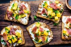 Grzanki z kremowym serem, baleronu jamon serrano i mango, słuzyć na drewnianej desce z czerwonym winem, szarości łupkowy tło, wie Obraz Royalty Free