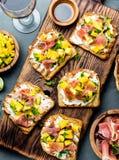 Grzanki z kremowym serem, baleronu jamon serrano i mango, słuzyć na drewnianej desce z czerwonym winem, szarości łupkowy tło, wie Zdjęcie Stock